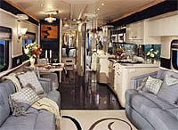 Inside view of a American Heritage looking from the front door to the back of the coach. The interior is white and black with gray leather seats.