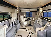 Inside view of a American Heritage looking from the back of the coach to the front. The interior is white and black with gray leather seats.