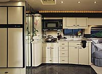 Inside view of a American Heritage showing the kitchen. The interior is white and black with the cabinets all white.
