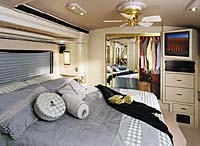 Inside view of a American Heritage showing the master bedroom. The interior is white and black with the sheets gray and a white and gold ceiling fan in the room .