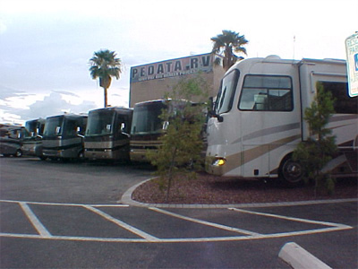 A picture of Pedata's sign with five motorhomes in front of the sign.